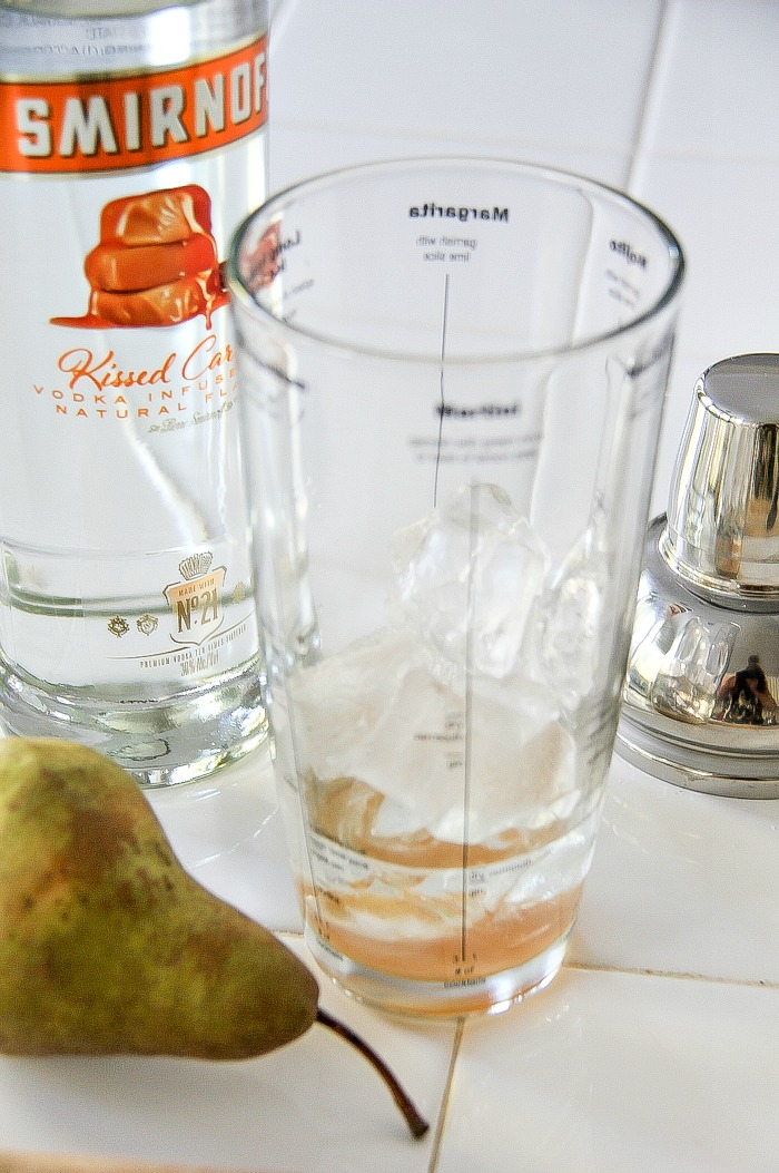 a cocktail shaker with vodka and a pear