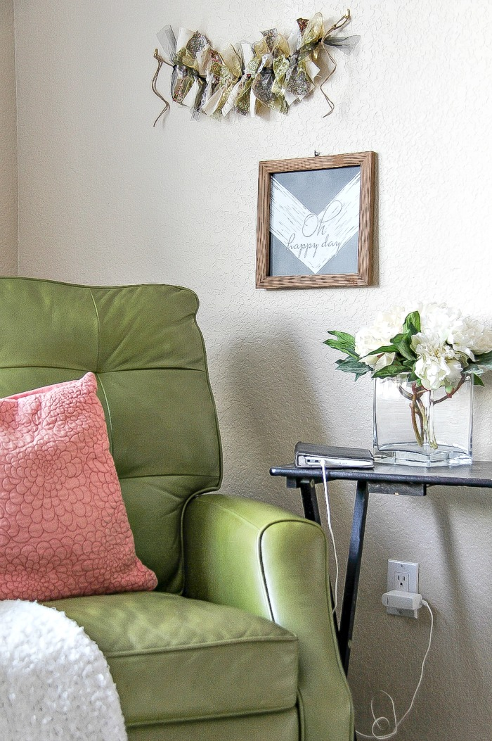 green recliner with side table and wall art