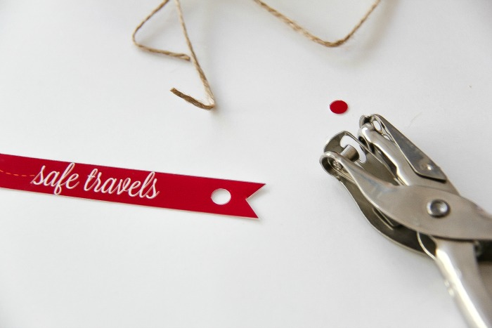 red and white safe travels gift tag with hole punch