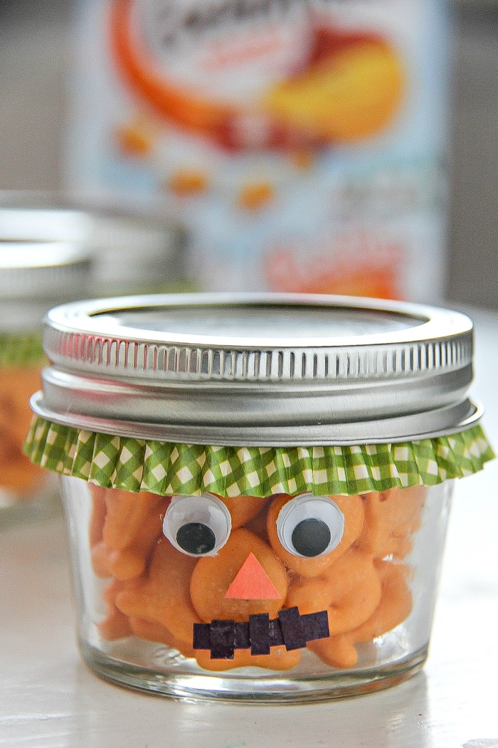 a fall treat jar turned into a scarecrow and filled with goldfish crackers