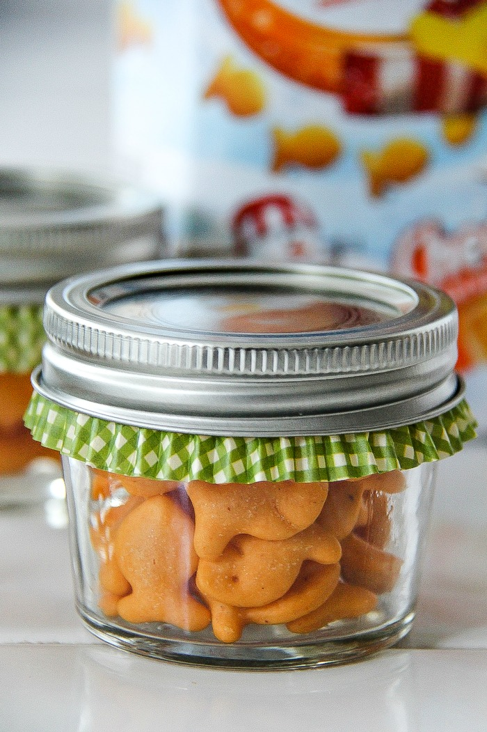 a canning jar filled with goldfish crackers and a green cupcake liner inside it