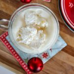 a white chocolate hot chocolate in a glass with red christmas ornaments