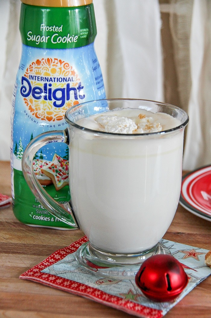 white hot chocolate in a glass with international delight sugar cookie creamer in the background