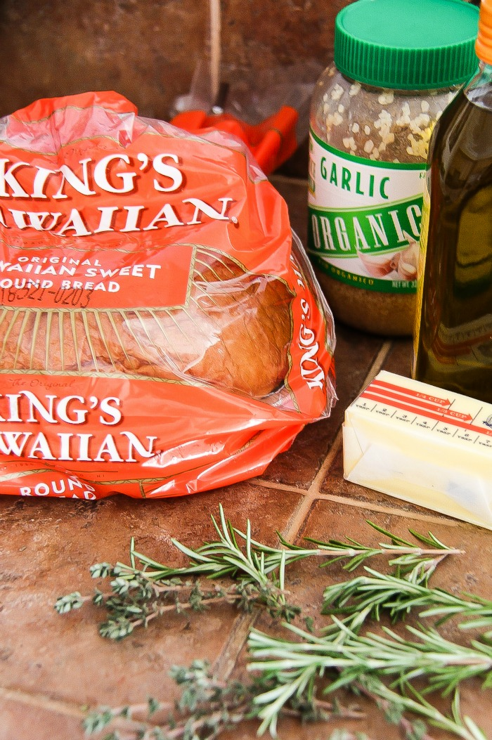 kings hawaiian sweet round bread with a jar of crushed garlic, stick of butter, and fresh rosemary and thyme.