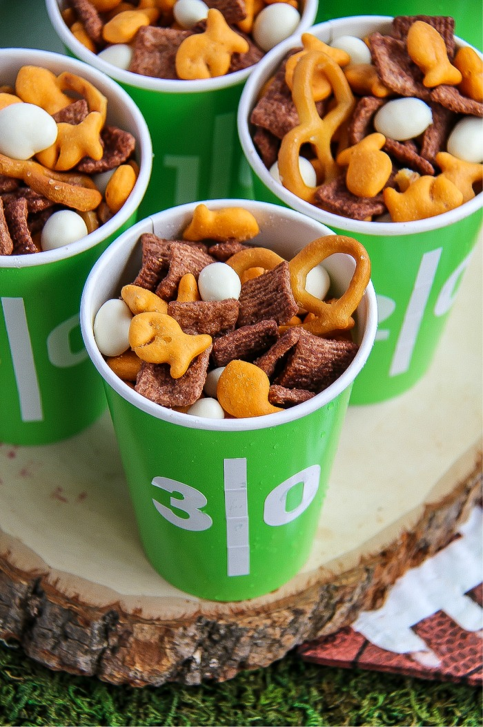 goldfish, pretzels and other snacks in football themed green and white cups
