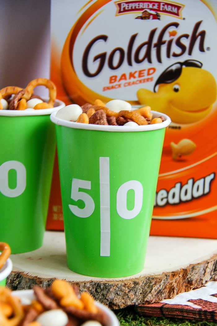 green and white football themed cups filled with snacks with a box of Goldfish crackers in the background