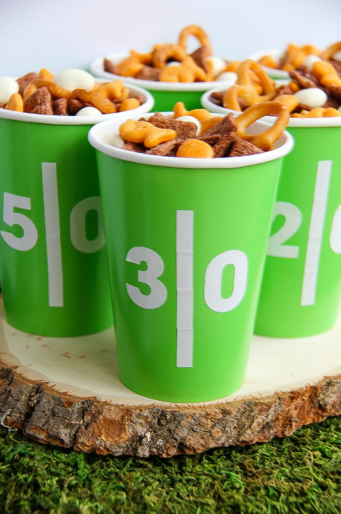 green and white football yard line cups filled with snack mix