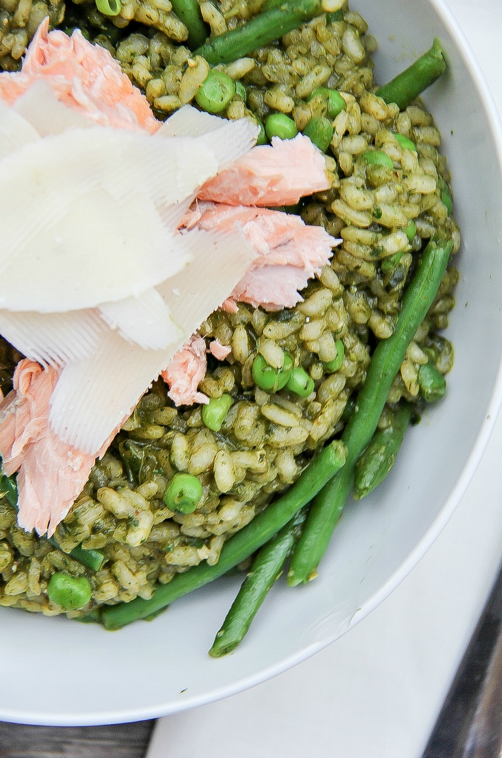 looking down on a white bowl filled with pesto risotto, peas, salmon, and cheese