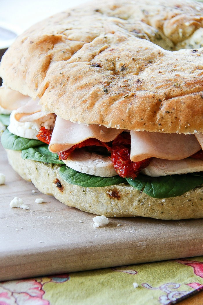 a focaccia sandwich filled with turkey, mushrooms, sundried tomatoes, and spinach