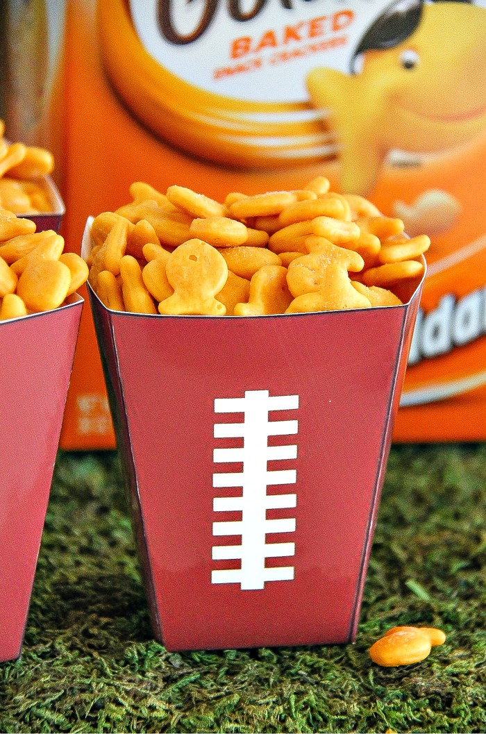 yellow goldfish crackers in a football paper cup with a box of goldfish in the background