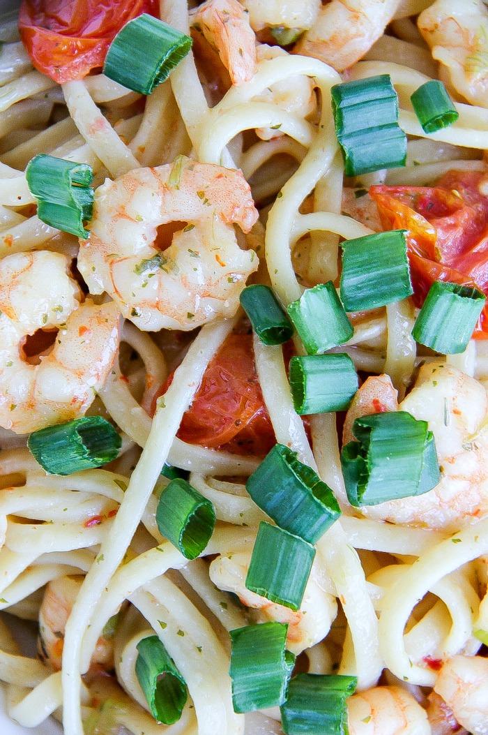 a photo of shrimp scampi up close with shrimp, linguine, green onions, and tomato