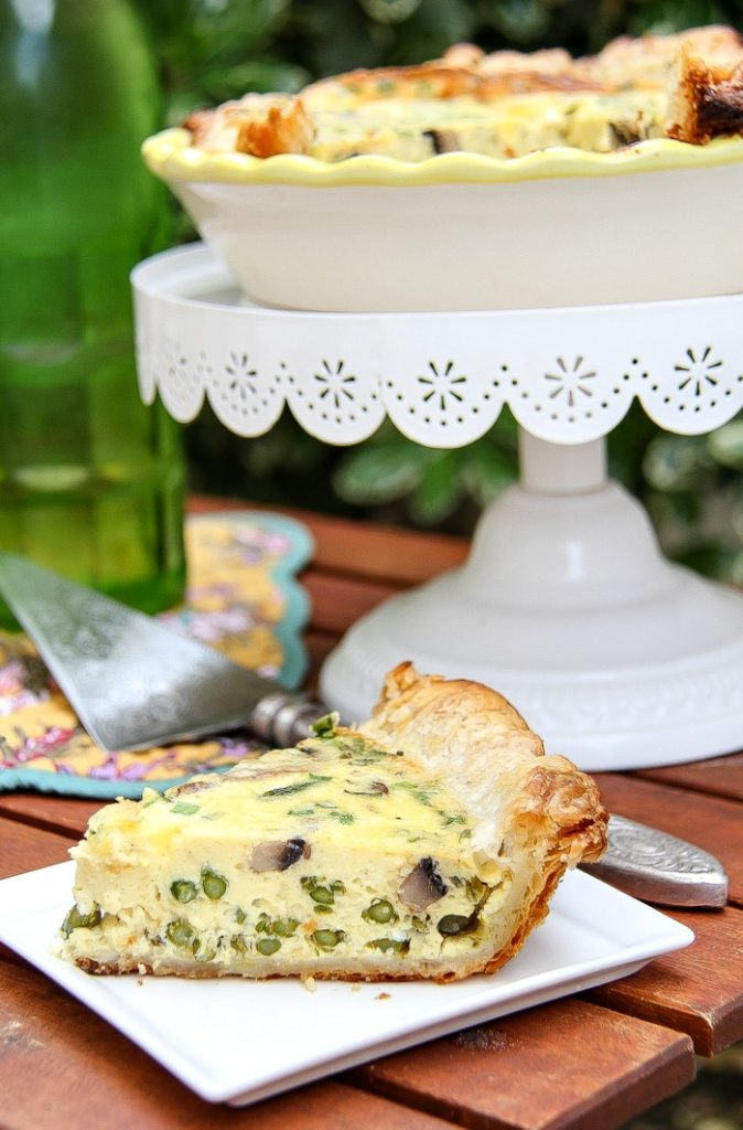 A cake stand with an asparagus and mushroom quiche with a slice on a plate underneath it