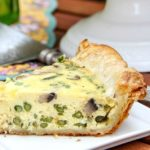 a slice of asparagus and mushroom quiche on a white plate