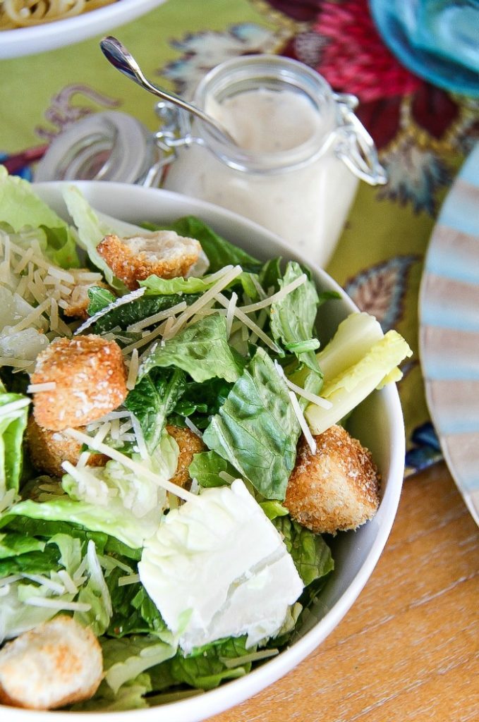A serving bowl of Caesar salad with a jar of dressing on the side