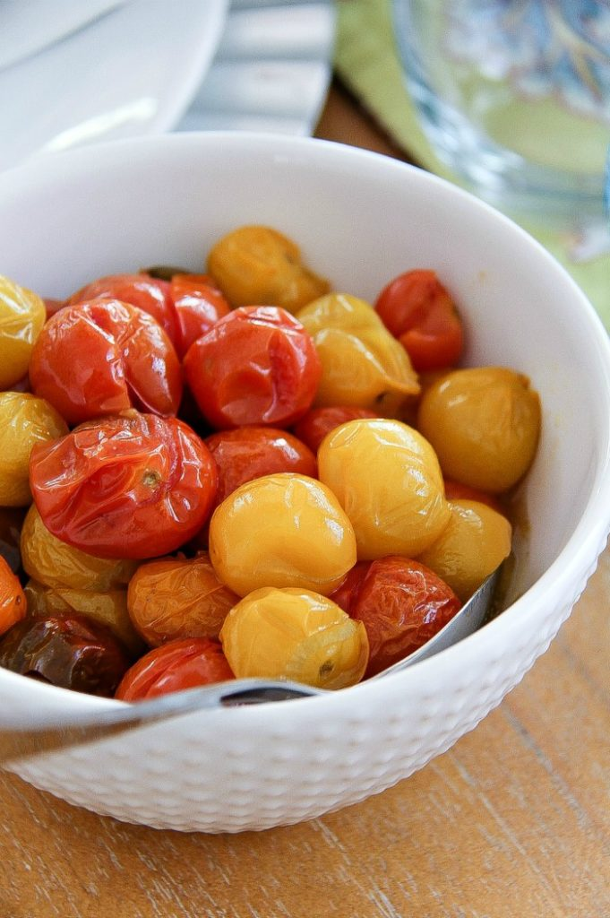 a white bowl filled with yellow and red mini heirloom tomatoes