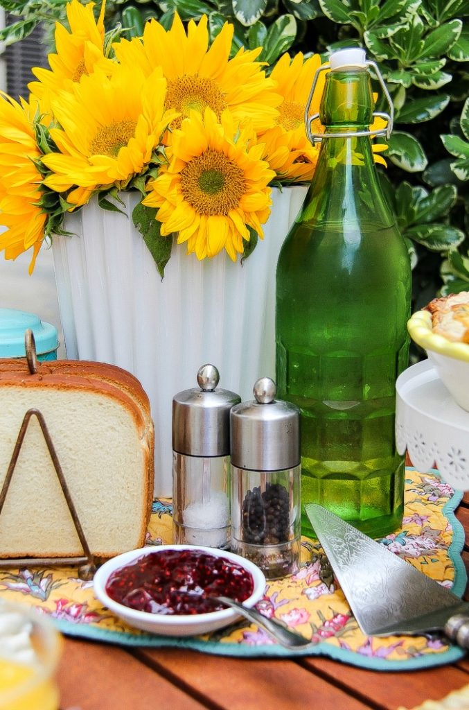Raspberry jam and toast in a toast holder in front of fresh sunflowers in a vase