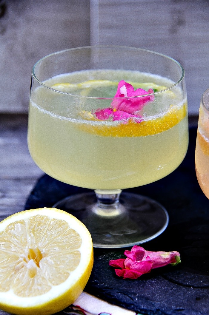 lemon cocktail with gin and prosecco in a cocktail glass garnished with a pink flower and lemon slice