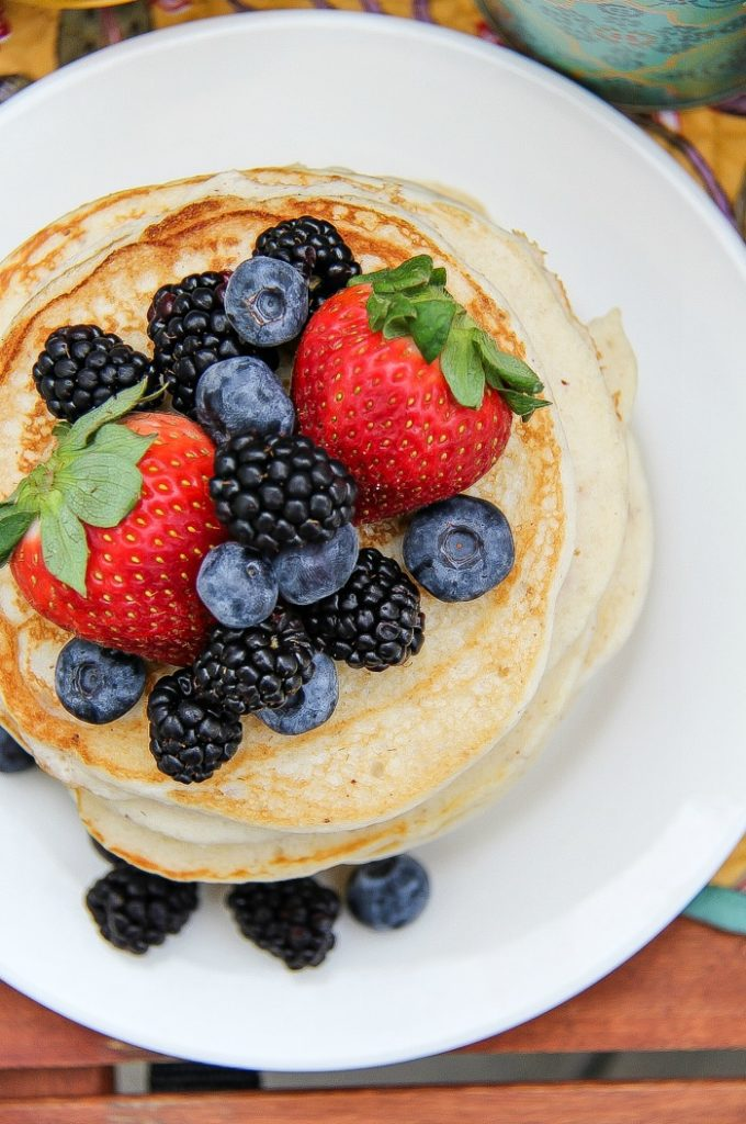 Looking down on a stack of pancakes on a white plate topped with fresh blueberries, blackberries, and strawberries