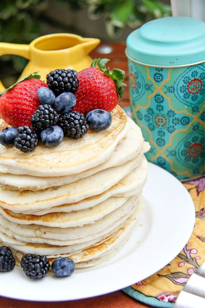 A stack of pancakes topped with fresh blueberries, blackberries, and strawberries.