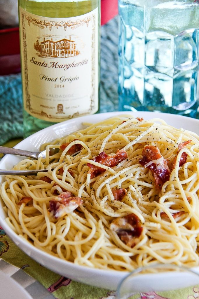 spaghetti carbonara and bacon in a white bowl with a bottle of pinot grigio in the background