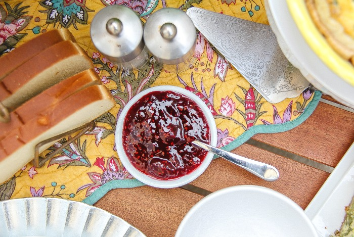 raspberry jam and fresh bread on a table for brunch