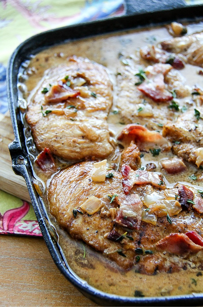 a cast-iron skillet with chicken breasts and bacon in a creamy sauce