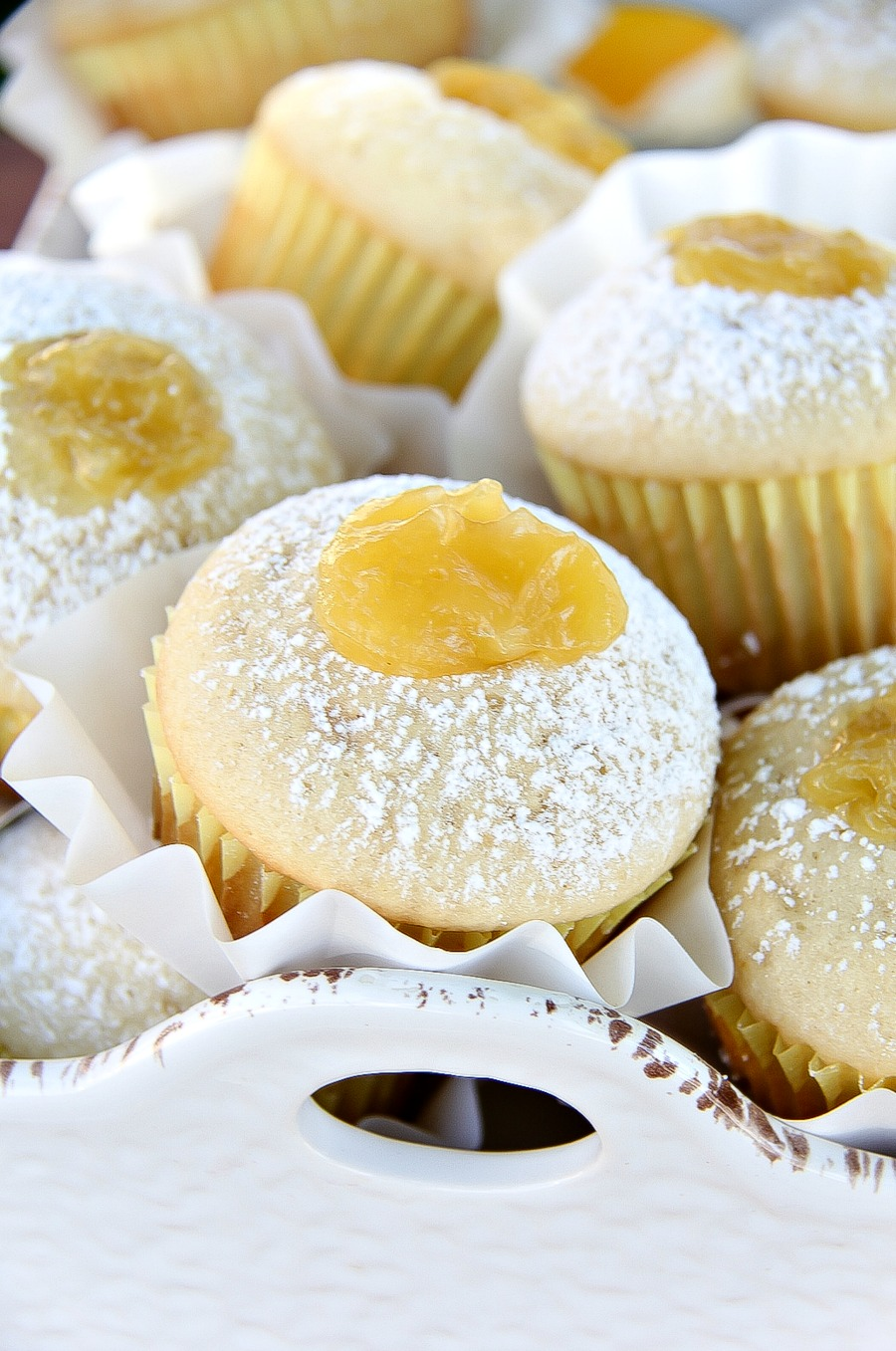 muffins in a white tray with lemon curd on top and confectioners sugar sifted over them