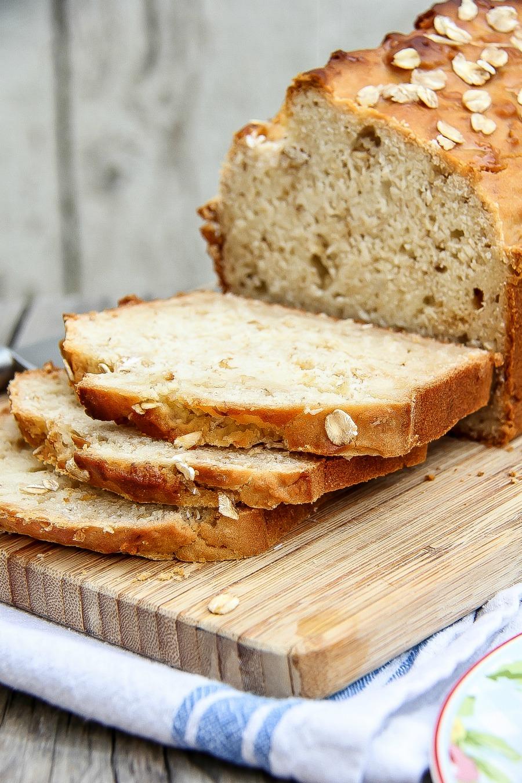 Homemade gluten-free honey oat bread sliced on a cutting board