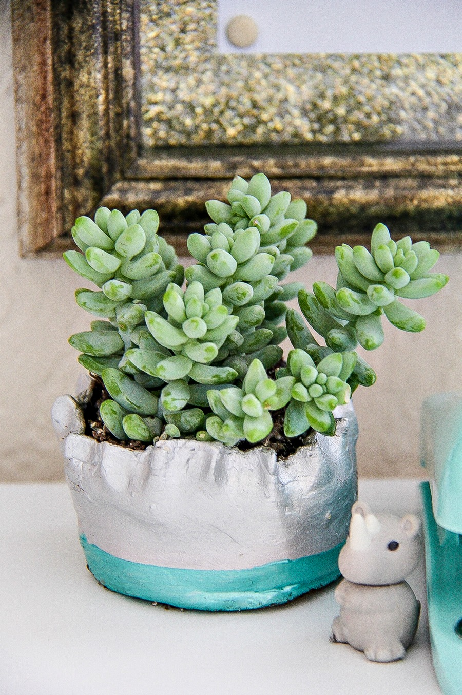 A handmade clay planter painted silver and blue with a succulent planted inside it.