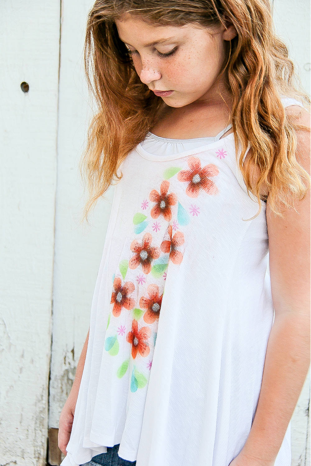 a girl wearing a white tank that has airbrush flowers on it