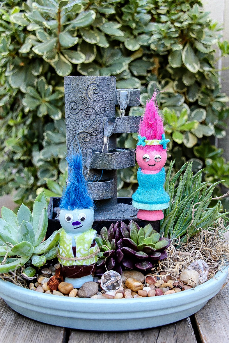 Handmade Trolls inside a container fairy garden with succulents and a water feature.