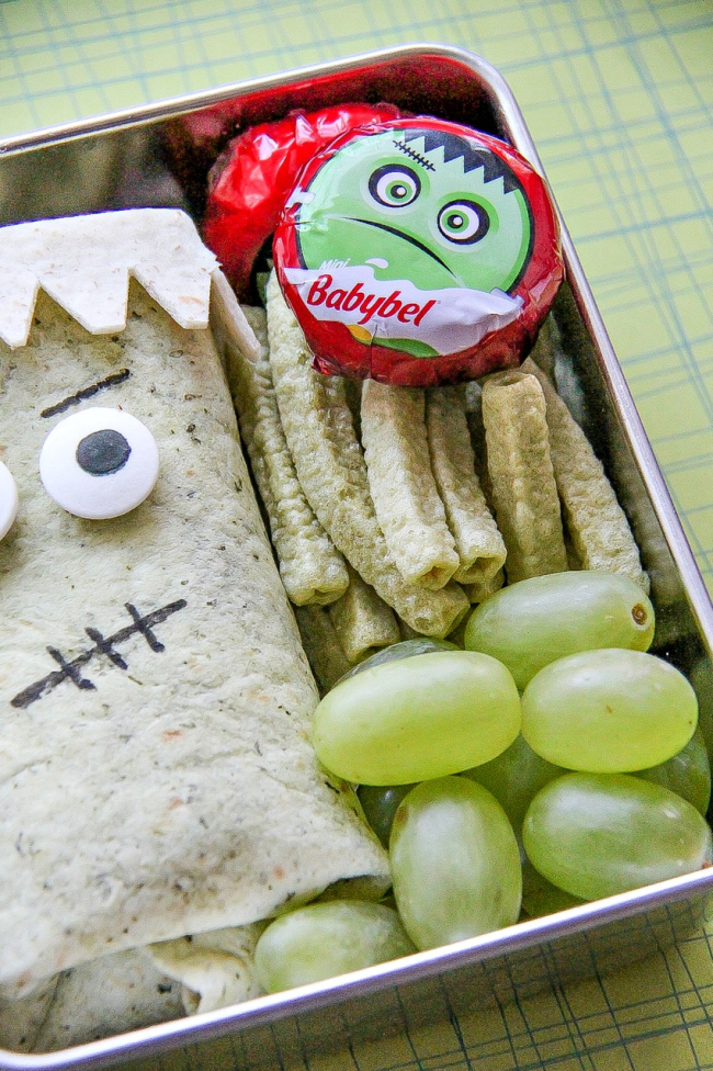 Frankenstein Friday Halloween treats for kids including a sandwich wrap and fruit.