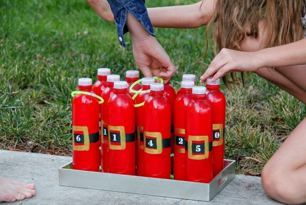 kids playing a handmade santa ring toss game with plastic bottles