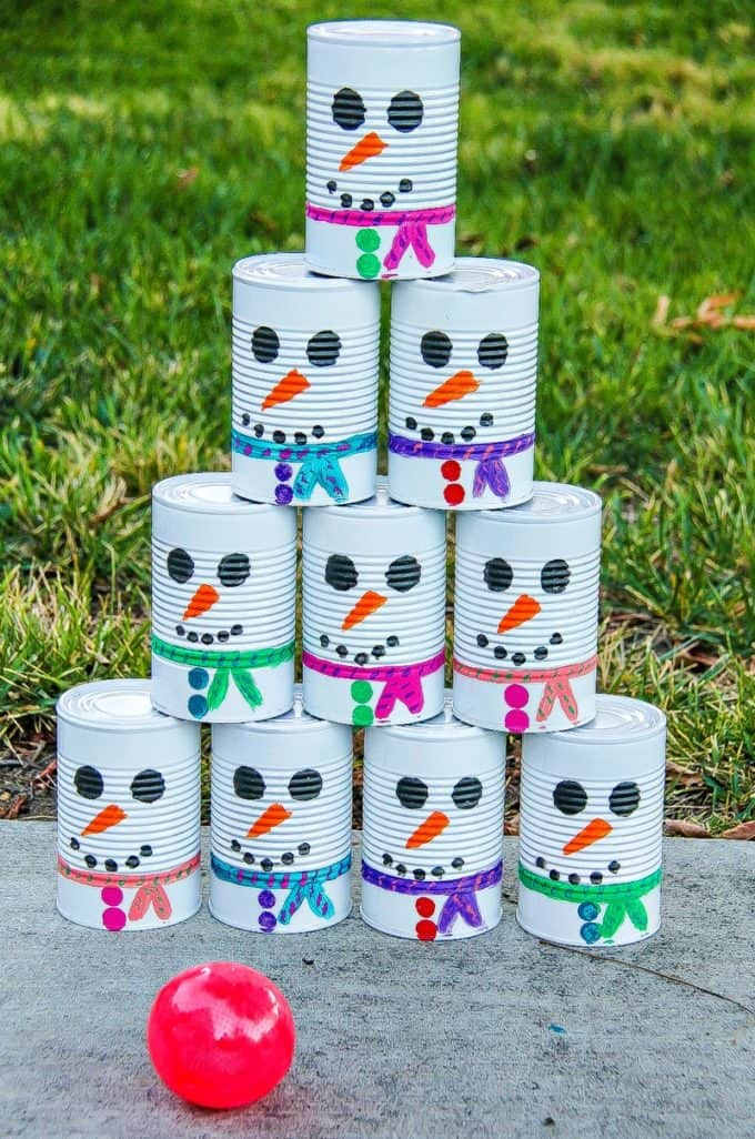 empty tin cans painted to look like a snowman for a tin can toss game with a ball