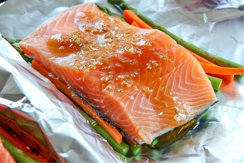 Salmon foil packets with asparagus and carrots with a honey glaze.