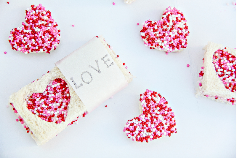 Miniature heart-shaped fairy bread and fairy bread sandwiches for Valentine's Day.