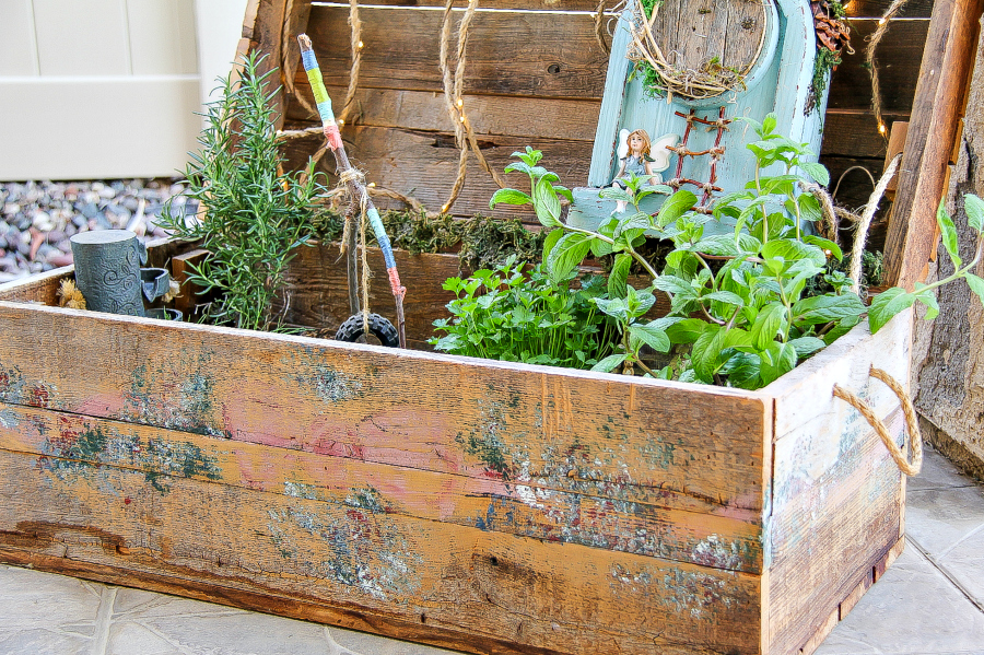 A large wood box with handles that has been turned into a fairy garden.