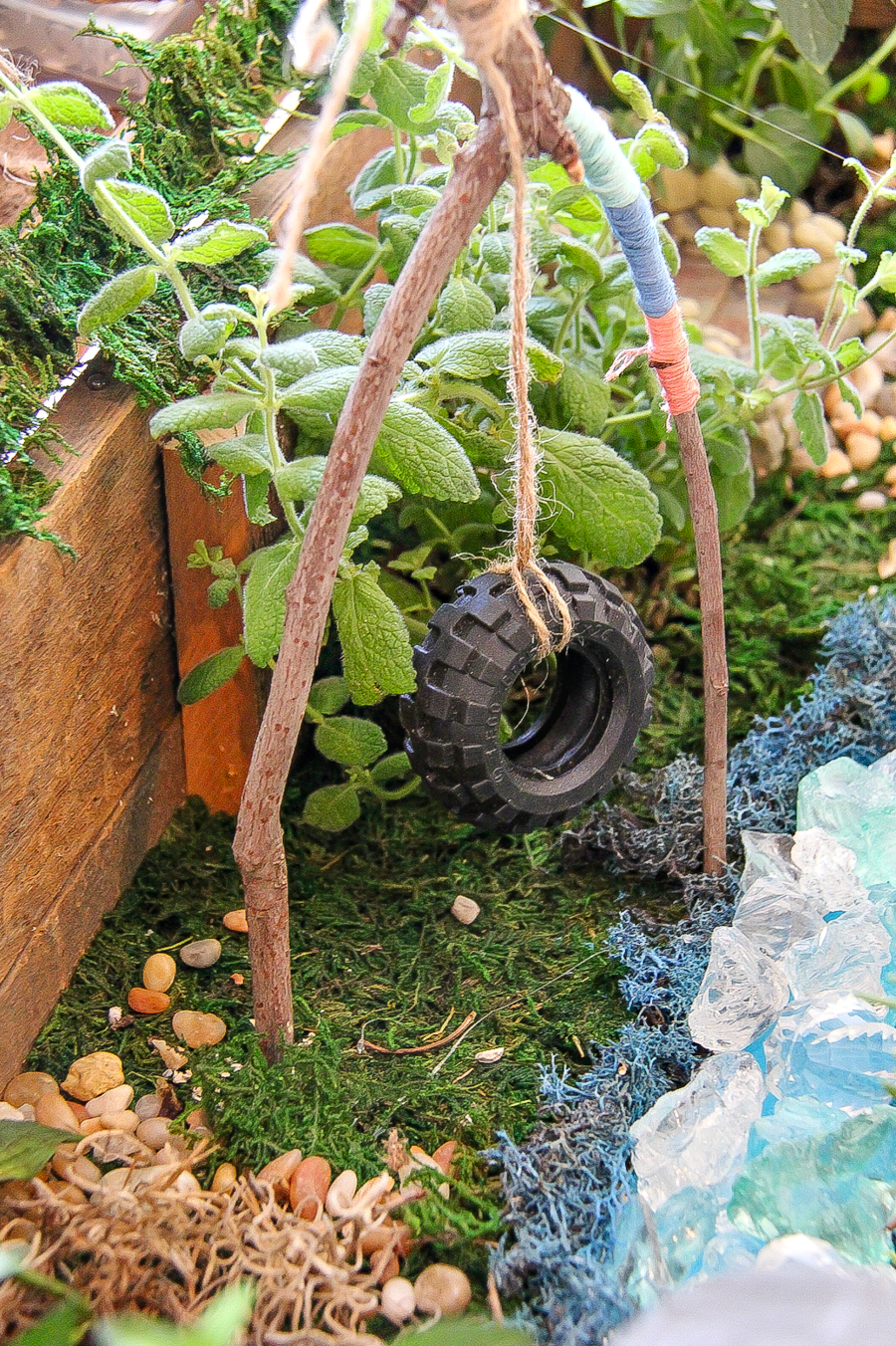 A tire swing for a fairy garden made out of a toy tire from a car and a stick wrapped with string.