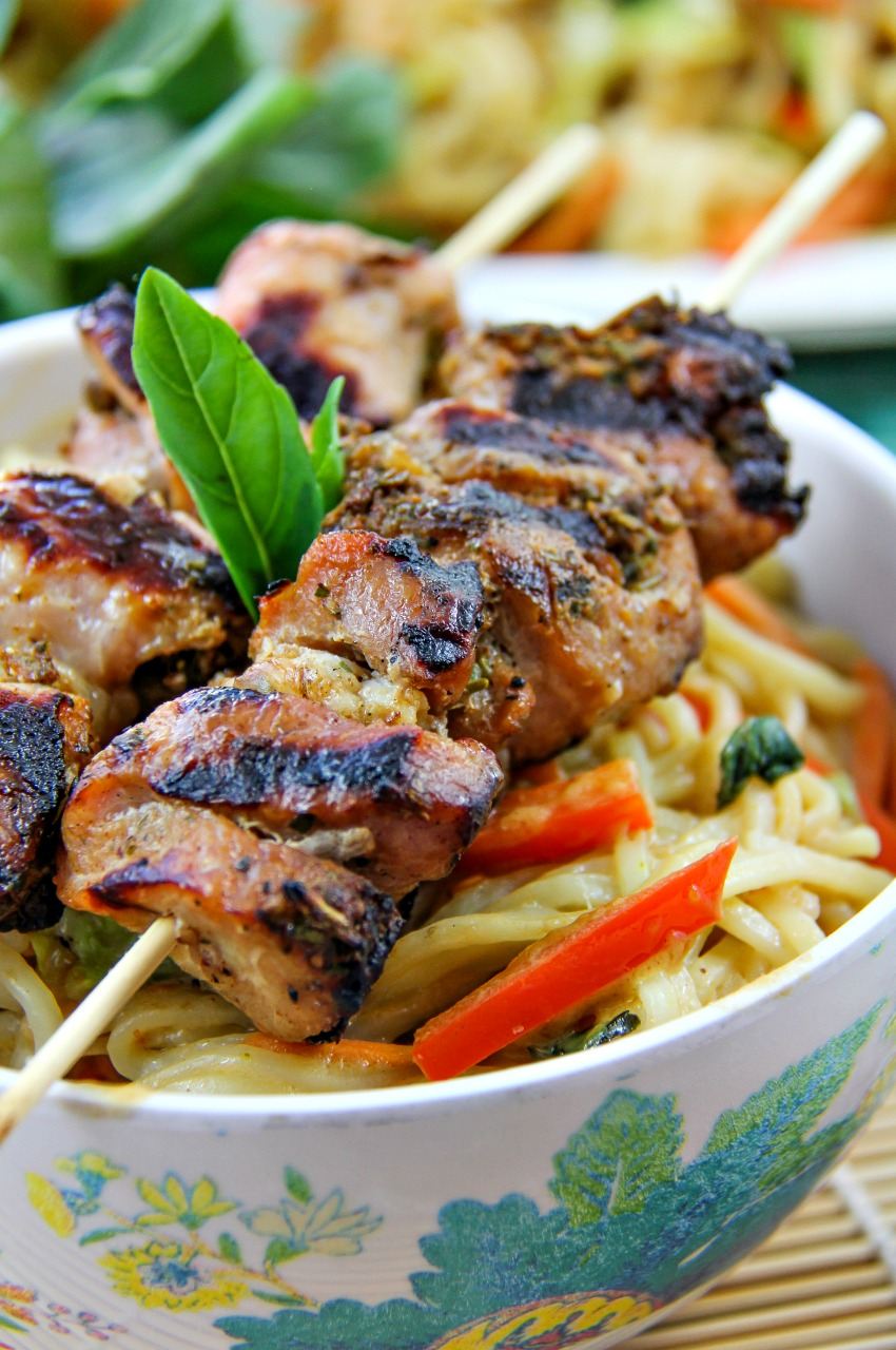 Marinated pork kebabs in a bowl on top of a spicy Asian noodle salad.