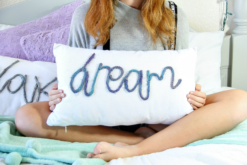 a white pillow with rope on it that spells the word dream
