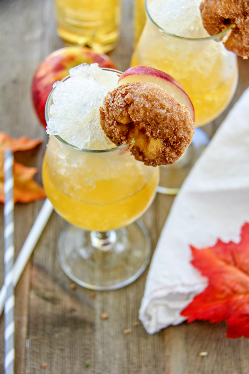 A cinnamon apple slush in a glass and garnished with an apple slice and cinnamon donut.
