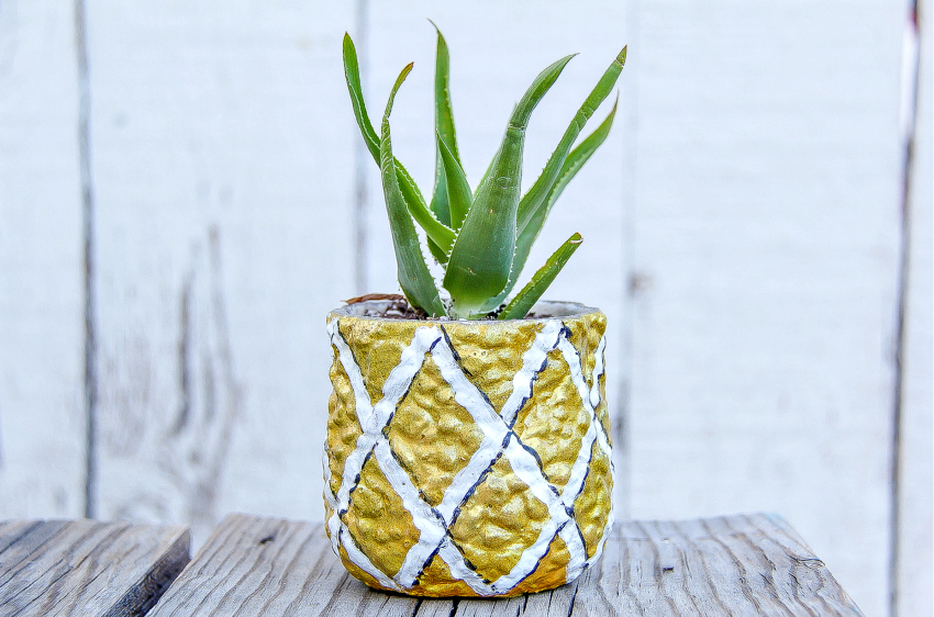 A pot painted like a pineapple with a succulent planted inside.