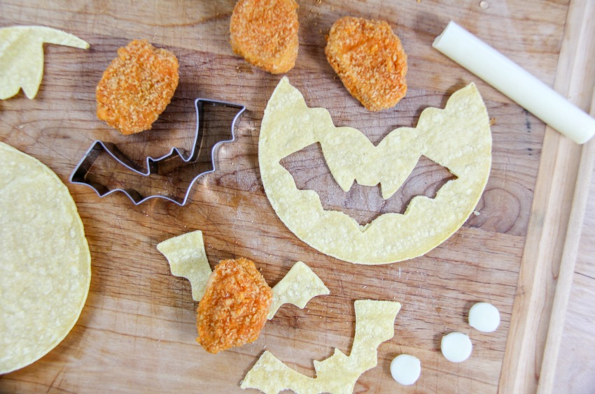 Bat wings being made out of tortillas for Halloween party food.