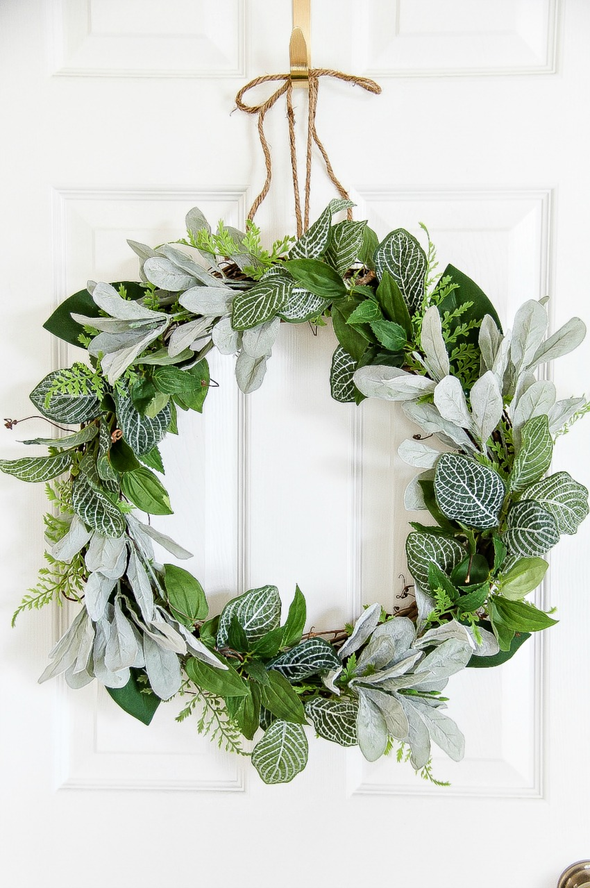 A simple round door wreath made with greenery and a stick circle