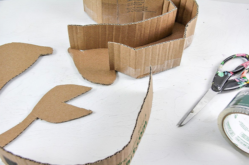 A DIY pull-string pinata being made out of a cardboard box.