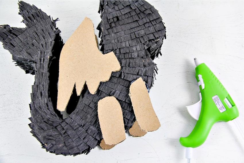 A black DIY pull-string dragon pinata being made.