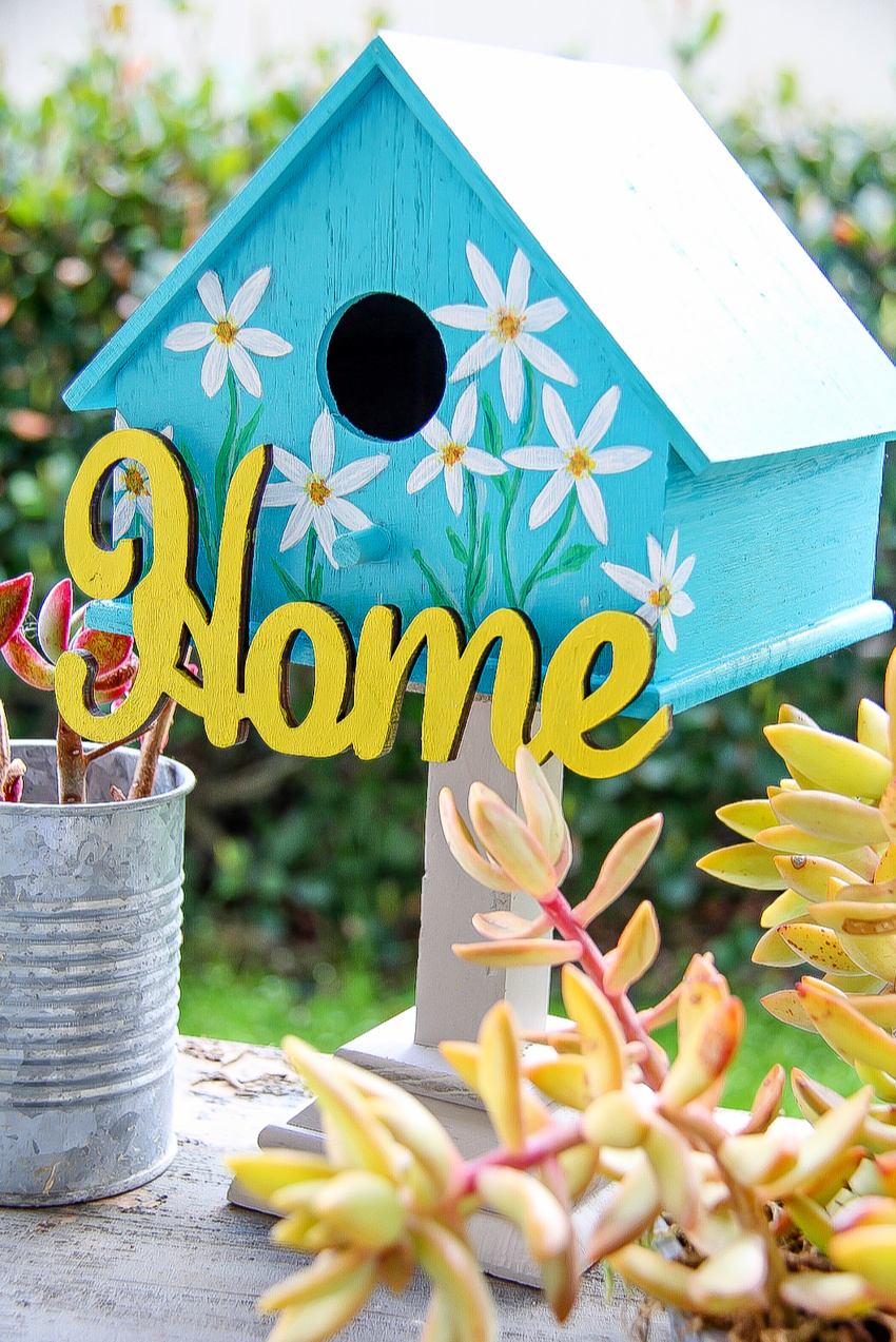 a birdhouse painted blue with flowers on it and a home sign in yellow