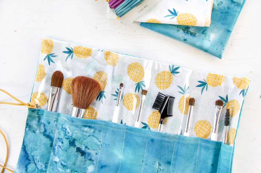 a handmade makeup brush roll in pineapple and blue fabric