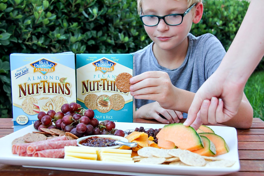 A kid with a gluten-free charcuterie board that has Blue Diamond Nut Thins.