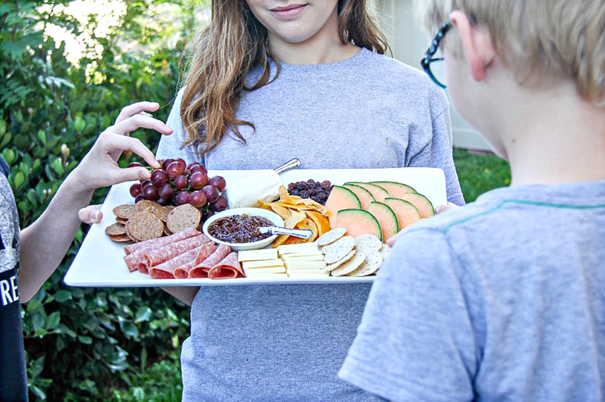 Kids sharing a gluten-free snack tray with cheese, fruit, crackers, and meats.